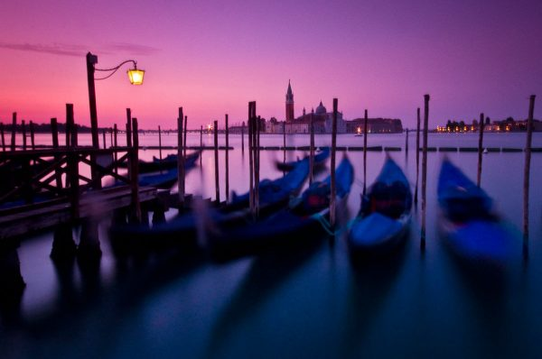 Gondolas gently rocking side to side, basking in the glory of the morning golden hour, in the waters of the Grand Canal in Venice, Italy.